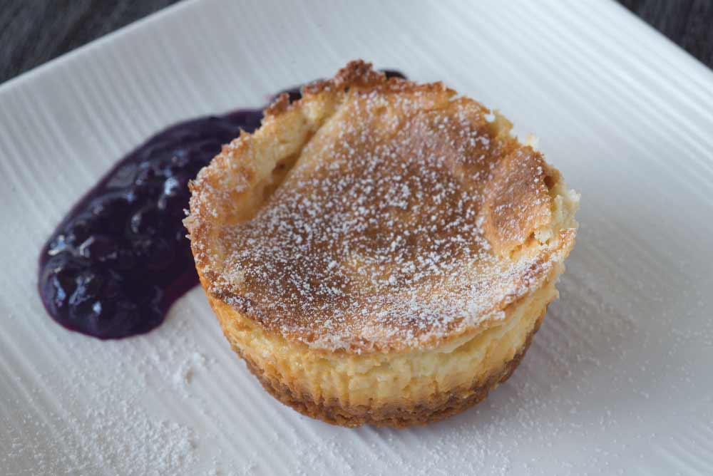 Miniature Cheesecake with Brown Sugar-Almond Crust in Warm Blueberry Sauce
